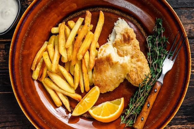 Fish and chips fast food britânico com batata frita e molho tártaro em prato rústico