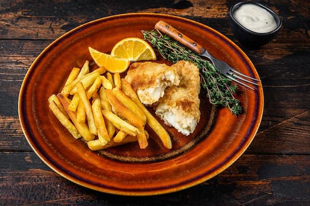Fish and chips fast food britânico com batatas fritas e molho tártaro em um prato rústico. fundo de madeira escuro. vista do topo.