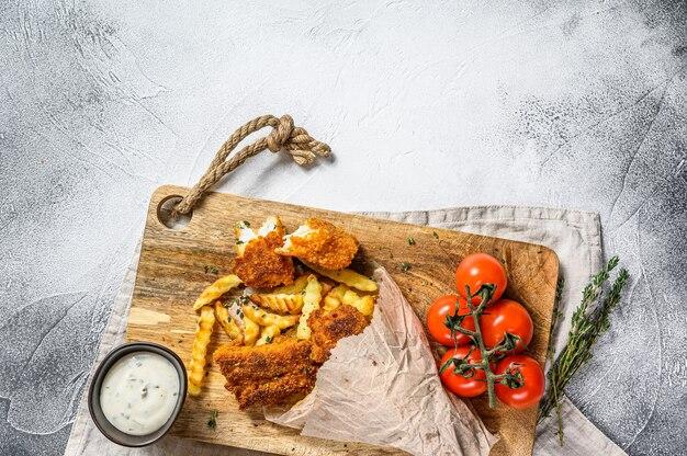 Fish and chips, fast food britânico servido com molho tártaro. fundo cinza