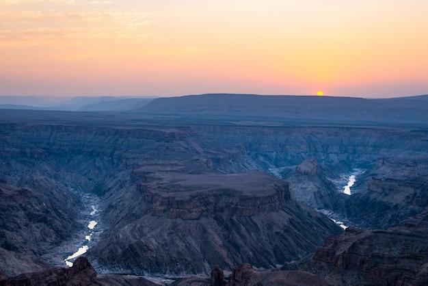 Fish river canyon, destino de viagem cênica no sul da namíbia. última luz solar nos cumes das montanhas. visão de grande angular de cima.