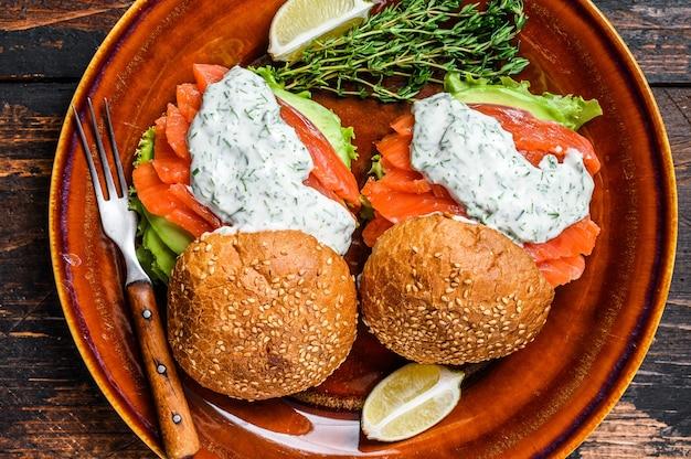 Fishburger com salmão de peixe salgado, abacate, pão de hambúrguer, molho de mostarda e salada de iceberg.
