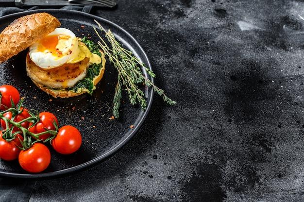 Fishburger delicioso com filé de peixe, ovo e espinafre em um bolo de brioche. superfície preta. vista do topo. copie o espaço