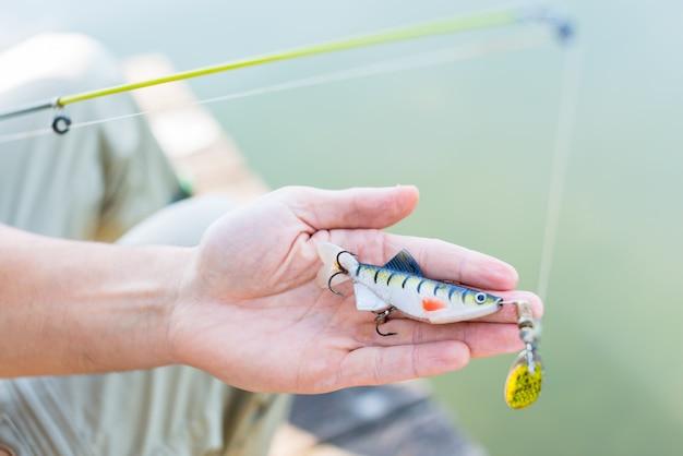 Fisher mostrando isca ou isca na vara de pesca