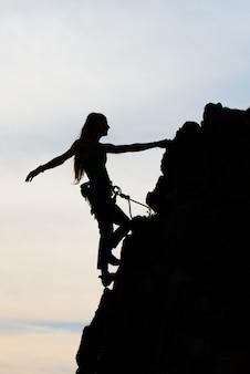 Físico bonito da mulher que escala uma parede rochosa