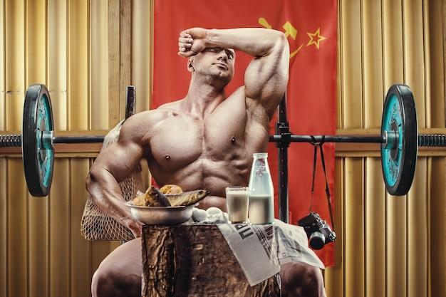 Fisiculturista à moda antiga fazendo exercícios no ginásio da velha escola, olhando para a seringa, injetor. estilo de homem bonito esportes caucasiano dos anos 80. estilo de vida soviético do esporte. conceito de urss e anos 80