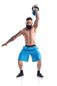Fisiculturista atleta masculino barbudo tatuado sem camisa e musculoso treino com kettlebell