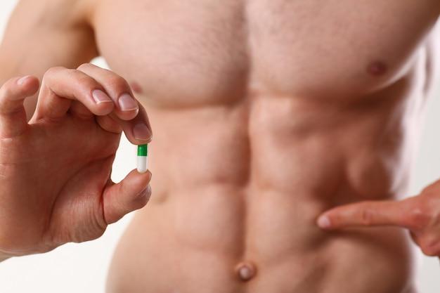 Fisiculturista atleta toma droga sob a forma de comprimidos, forma farmacêutica, progresso rápido no desenvolvimento muscular