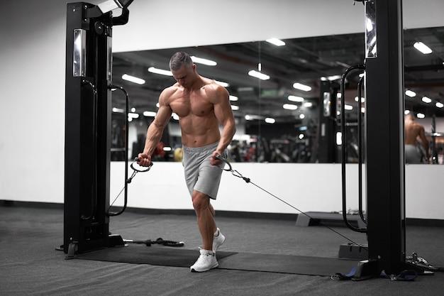 Fisiculturista atlético muscular em pé, treinando os músculos do peito e dos ombros em equipamentos de ginástica