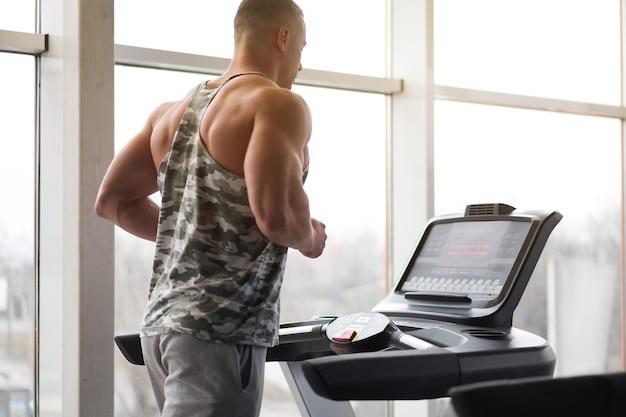 Fisiculturista atlético musculoso e fitness modelo correndo na esteira perto de uma janela grande