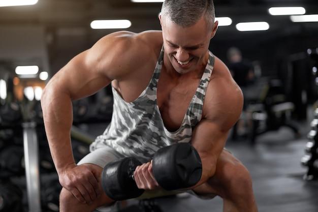 Fisiculturista atlético musculoso modelo fitness sentado no banco treinando bíceps levantando halteres no ginásio coberto