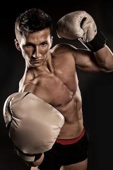 Fisiculturista atlético pose em calças. boxer com o peito nu. esporte e treino. gladiador ou atlant em luvas de boxe. homem com corpo musculoso.