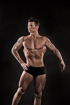 Fisiculturista atlético pose em calças. homem com corpo musculoso. esporte e treino. adam com o peito nu. gladiador ou atlant.