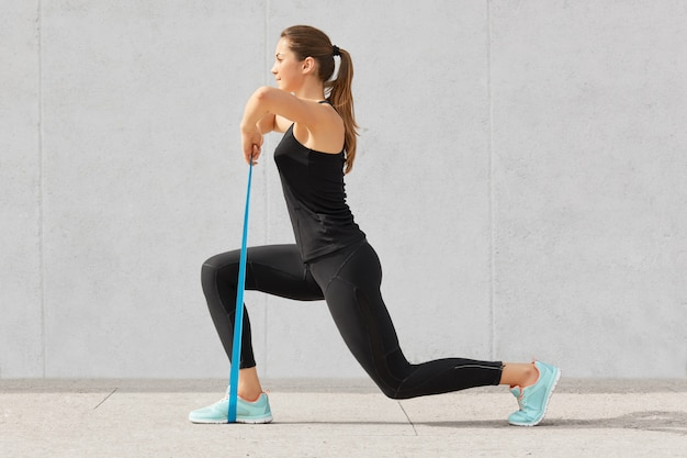 Fisiculturista autodeterminado faz exercícios com elástico, trabalha nas mãos e nas pernas, usa tênis e roupas esportivas confortáveis