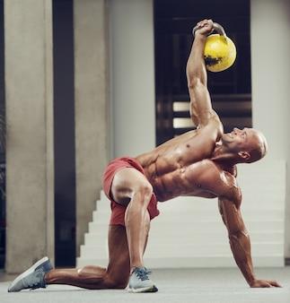 Fisiculturista bombeando os músculos do peito com kettlebell