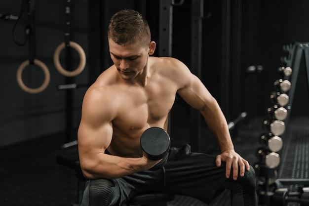 Fisiculturista bonito e poderoso homem atlético fazendo exercícios com halteres em uma academia