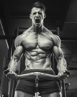 Fisiculturista bonito forte atlético áspero homem bombeando músculos bíceps, fitness, treino e conceito de musculação