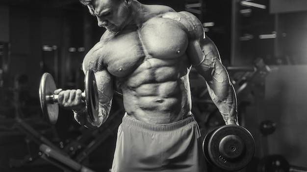 Fisiculturista bonito forte atlético áspero homem bombeando os músculos do bíceps, exercícios, fitness e conceito de musculação