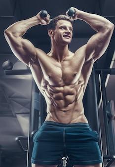 Fisiculturista bonito forte atlético áspero homem bombeando os músculos do tríceps, exercícios, fitness e conceito de musculação