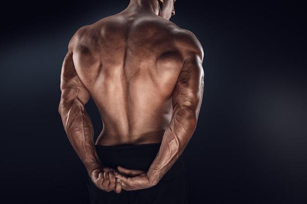 Fisiculturista bonito poder mostrando as costas