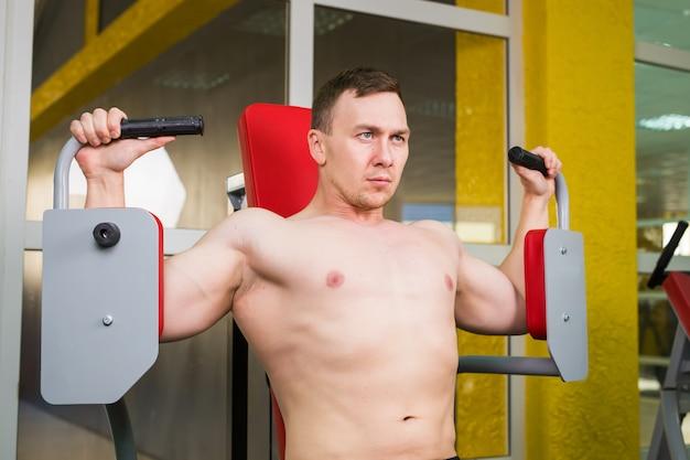 Fisiculturista bonito trabalha exercício no ginásio