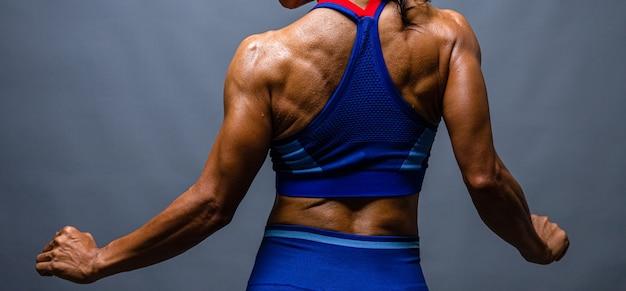 Fisiculturista careca forte com tanquinho. mulher fisiculturista com abs perfeito, ombros, bíceps, tríceps e peito, personal trainer flexionando seus músculos.