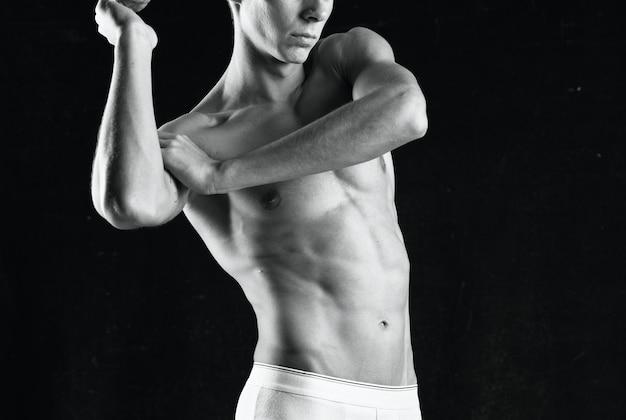 Fisiculturista com corpo forte usando calcinha branca posando com fundo escuro