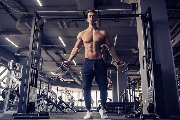 Fisiculturista de aptidão muscular fazendo exercícios pesados para músculos peitorais na máquina com cabo na academia