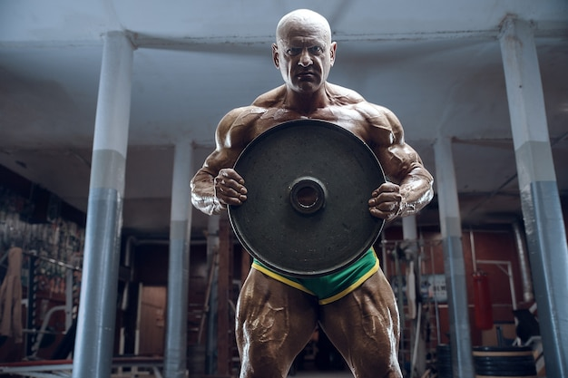 Fisiculturista de atleta à moda antiga fazendo exercícios de braço no ginásio. brutal careca esportes caucasianos homem estilo dos anos 80. conceito de esporte, fitness e treino dos anos 80