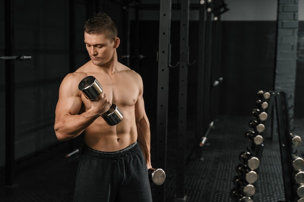 Fisiculturista de atlético homem bonito poder fazer exercícios com halteres em um ginásio.