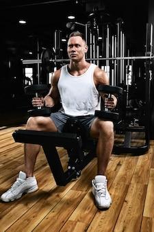 Fisiculturista de cara musculoso fazendo exercícios com halteres no ginásio. corpo atlético, estilo de vida saudável, motivação de fitness, corpo positivo.
