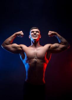 Fisiculturista de homem atlético poder bonito. corpo musculoso de aptidão em fundo escuro de fumaça. macho perfeito. incrível fisiculturista, tatuagem, levantando as mãos. viktory.
