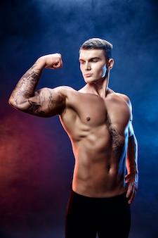 Fisiculturista de homem atlético poder bonito. corpo musculoso de aptidão na cena escura de fumaça. macho perfeito. incrível fisiculturista, tatuagem, posando.