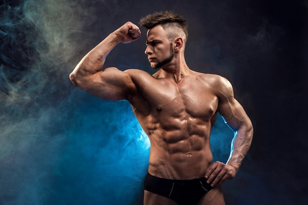 Fisiculturista de homem atlético poder bonito. corpo musculoso fitness molhado em fundo escuro de fumaça.