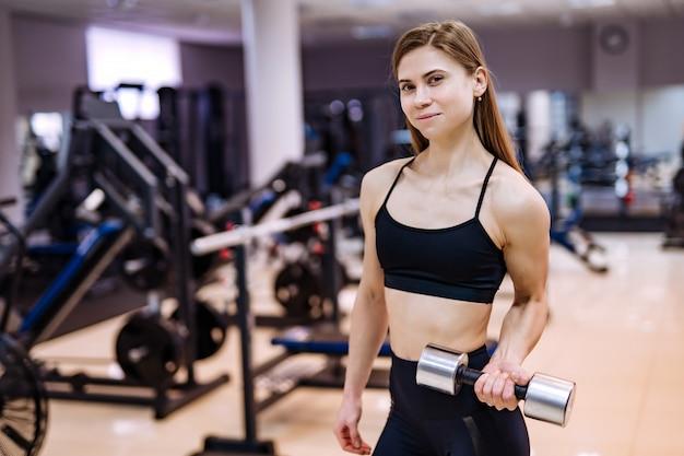 Fisiculturista de mulher muito sorridente, olhando para a câmera enquanto faz exercícios com halteres no centro esportivo.