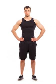 Fisiculturista em fitwear posando isolado