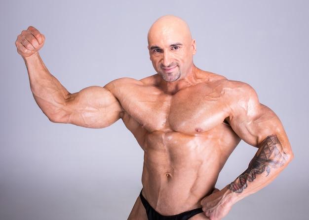 Fisiculturista está demonstrando seu corpo musculoso perfeito.