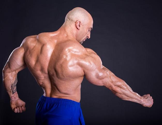 Fisiculturista está posando, mostrando seus músculos.