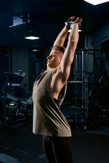 Fisiculturista, esticando a parte superior do corpo no ginásio.