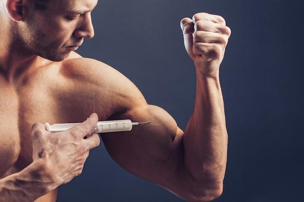 Fisiculturista faz foto de injeção de vitaminas de homem desportivo com físico perfeito em fundo escuro