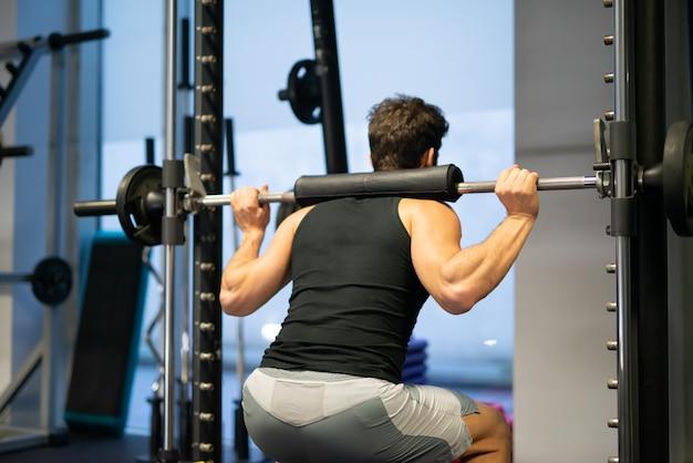 Fisiculturista fazendo agachamento usando uma gaiola de agachamento em uma academia para treinar as pernas