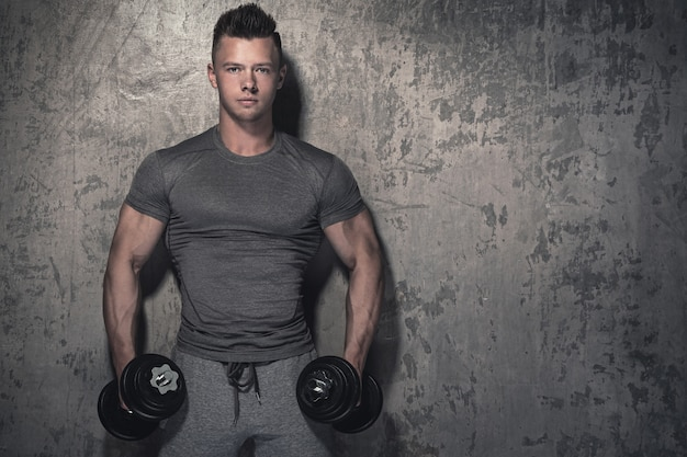 Fisiculturista fazendo bíceps cachos com halteres
