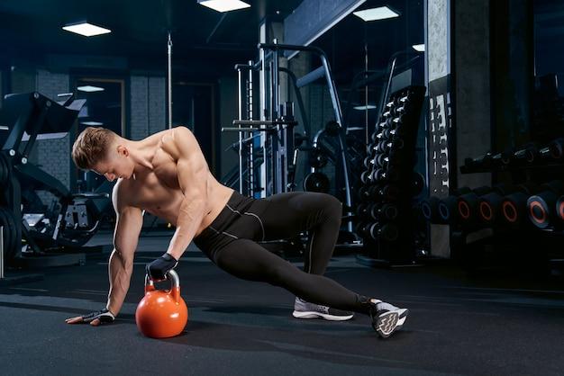 Fisiculturista fazendo exercício de prancha lateral.