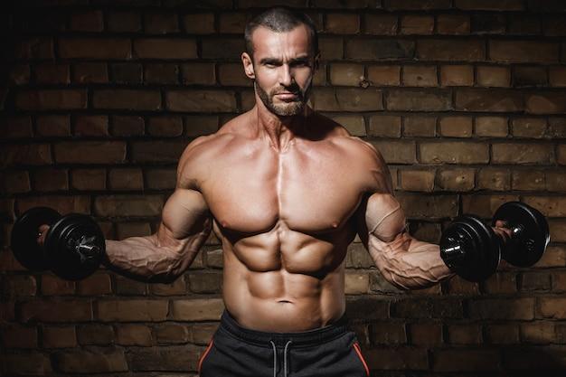 Fisiculturista fazendo exercícios para bíceps com halteres