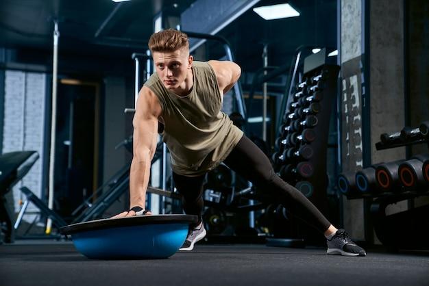Fisiculturista fazendo flexões por um lado.