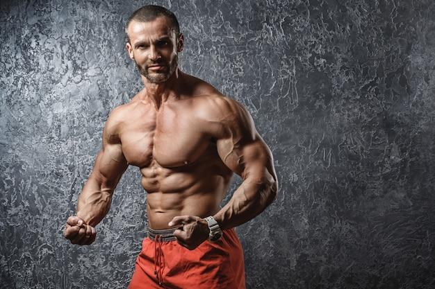 Fisiculturista forte e muscular, mostrando seu corpo