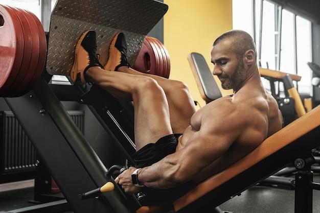 Fisiculturista forte e musculoso fazendo um exercício de leg press sentado em uma academia