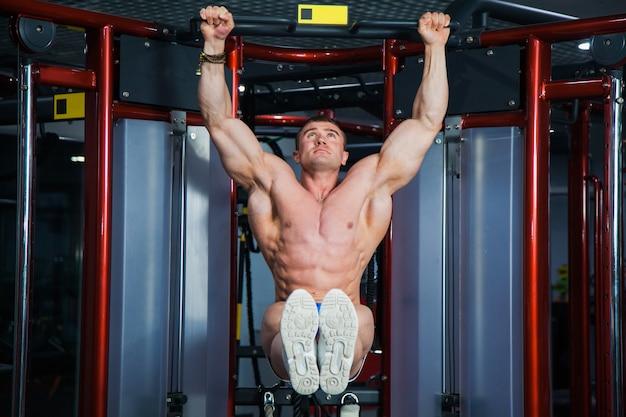 Fisiculturista forte e musculoso se exercitando na academia