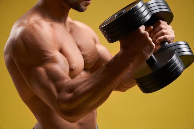 Fisiculturista forte fazendo exercício com halteres