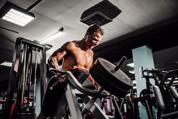 Fisiculturista forte fazendo exercício de peso pesado para as costas na máquina. exercício t-pull