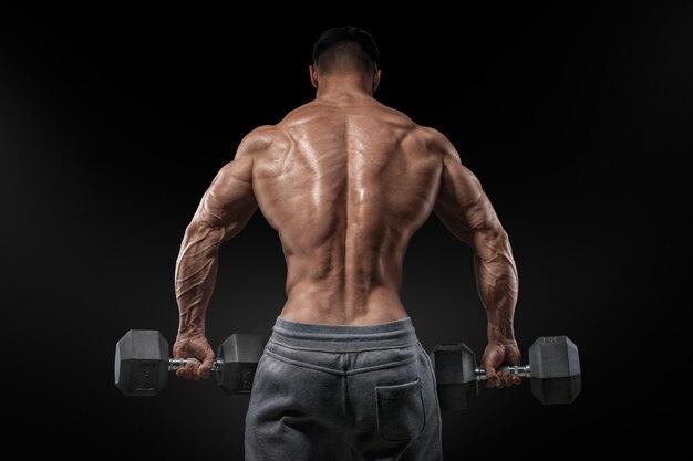 Fisiculturista forte fazendo exercícios com halteres voltados para trás